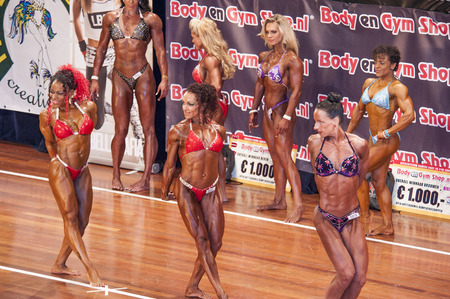 national championship: SCHIEDAM, THE NETHERLANDS - APRIL 26, 2015: Female bikini models Evelien Nellen, Maria Wattel showing their best at the 38th Dutch National Championship Bodybuilding and Fitness of the IFBB Netherlands (NBBF) on april 26, 2015 in Theatre aan de Schie at