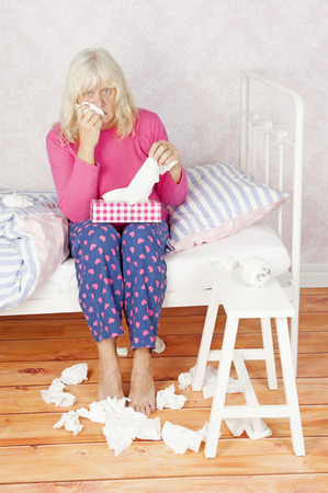 heartbreak issues: Worrying female with pink pajama and tissues sitting on bed