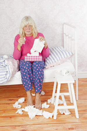 heartbreak issues: Sick woman with pink pajama and tissues sitting on bed