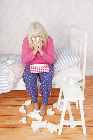 heartbreak issues: Sick lady with pink pajama and tissues sitting on bed blowing her nose
