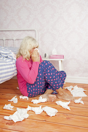 heartbreak issues: Sick woman with pink pajama and tissues sitting on floor against bed