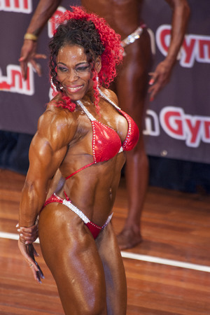 schiedam: SCHIEDAM, THE NETHERLANDS - APRIL 26, 2015: Female bikini model Lisandra Chacon shows her best triceps pose at the 38th Dutch National Championship Bodybuilding and Fitness of the IFBB Netherlands (NBBF) on april 26, 2015 in Theatre aan de Schie at Schi