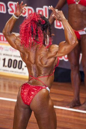 schiedam: SCHIEDAM, THE NETHERLANDS - APRIL 26, 2015: Female bikini model Lisandra Chacon shows her best back double biceps pose at the 38th Dutch National Championship Bodybuilding and Fitness of the IFBB Netherlands (NBBF) on april 26, 2015 in Theatre aan de Sch