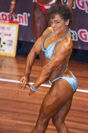 national championship: SCHIEDAM, THE NETHERLANDS - APRIL 26, 2015: Female bikini model Floor van Putten shows her best chest pose in blue bikini on stage at the 38th Dutch National Championship Bodybuilding and Fitness of the IFBB Netherlands (NBBF) on april 26, 2015 in Theatre