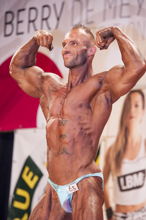schiedam: SCHIEDAM, THE NETHERLANDS - APRIL 26, 2015. Male bodybuilder shows his best double biceps pose on stage at the 38th Dutch National Championship Bodybuilding and Fitness of the IFBB Netherlands (NBBF) on april 26, 2015 in Theatre aan de Schie at Schiedam