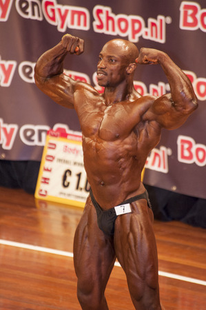 schiedam: SCHIEDAM, THE NETHERLANDS - APRIL 26, 2015. Male bodybuilder shows his best front double biceps pose on stage at the 38th Dutch National Championship Bodybuilding and Fitness of the IFBB Netherlands (NBBF) on april 26, 2015 in Theatre aan de Schie at Sc