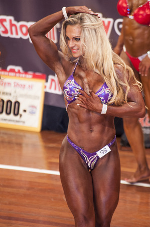 schiedam: SCHIEDAM, THE NETHERLANDS - APRIL 26, 2015: Female bikini model Evelien Nellen shows her best abdominals and thighs pose at the 38th Dutch National Championship Bodybuilding and Fitness of the IFBB Netherlands (NBBF) on april 26, 2015 in Theatre aan de S Editorial