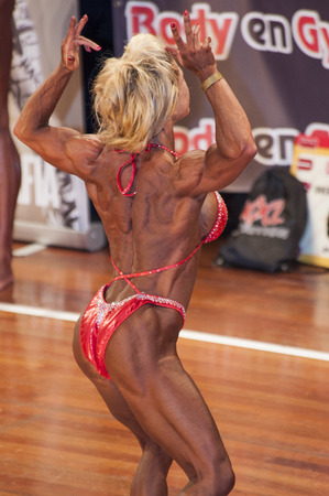 schiedam: SCHIEDAM, THE NETHERLANDS - APRIL 26, 2015: Female bikini model Sylvia Thijssen shows her best back double biceps pose at the 38th Dutch National Championship Bodybuilding and Fitness of the IFBB Netherlands (NBBF) on april 26, 2015 in Theatre aan de Sch