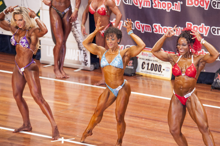schiedam: SCHIEDAM, THE NETHERLANDS - APRIL 26, 2015: Three female bikini models Lisandra Chacon, Floor van Putten and Evelien Nellen show their best front double biceps pose at the 38th Dutch National Championship Bodybuilding and Fitness of the IFBB Netherlands (