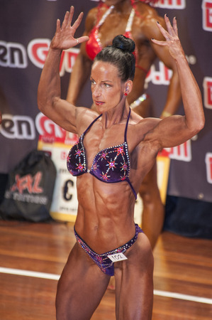 schiedam: SCHIEDAM, THE NETHERLANDS - APRIL 26, 2015: Female bikini model Mariska Meuwissen shows her best front double biceps pose at the 38th Dutch National Championship Bodybuilding and Fitness of the IFBB Netherlands (NBBF) on april 26, 2015 in Theatre aan de