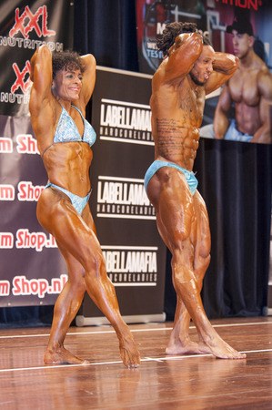 schiedam: SCHIEDAM, THE NETHERLANDS - APRIL 26, 2015: Bodybuilding duo Floor van Putten and Grego Francisca show their best abdominals and thighs pose on stage at the 38th Dutch National Championship Bodybuilding and Fitness of the IFBB Netherlands (NBBF) on april