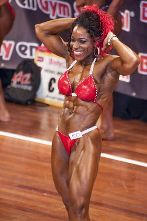 national championship: SCHIEDAM, THE NETHERLANDS - APRIL 26, 2015: Female bikini model Lisandra Chacon shows her best abdominals and thighs pose on stage at the 38th Dutch National Championship Bodybuilding and Fitness of the IFBB Netherlands (NBBF) on april 26, 2015 in Theatre Editorial