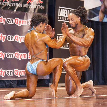 kneeled: SCHIEDAM, THE NETHERLANDS - APRIL 26, 2015: Bodybuilding duo Floor van Putten and Grego Francisca holding hands and kneeled on stage at the 38th Dutch National Championship Bodybuilding and Fitness of the IFBB Netherlands (NBBF) on april 26, 2015 in Theat