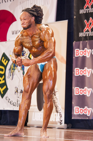 national championship: SCHIEDAM, THE NETHERLANDS - APRIL 26, 2015. Male bodybuilder Grego Francisca shows his best most muscular pose at the 38th Dutch National Championship Bodybuilding and Fitness of the IFBB Netherlands (NBBF) on april 26, 2015 in Theatre aan de Schie at S