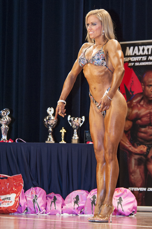 schiedam: SCHIEDAM, THE NETHERLANDS - APRIL 26, 2015: Female bodyfitness bikini model Lesley Barents shows her best front pose on stage at the 38th Dutch National Championship Bodybuilding and Fitness of the IFBB Netherlands (NBBF) on april 26, 2015 in Theatre aan
