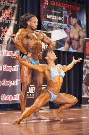 schiedam: SCHIEDAM, THE NETHERLANDS - APRIL 26, 2015: Bodybuilding duo Floor van Putten and Grego Francisca show their muscular body on stage at the 38th Dutch National Championship Bodybuilding and Fitness of the IFBB Netherlands (NBBF) on april 26, 2015 in Theatr