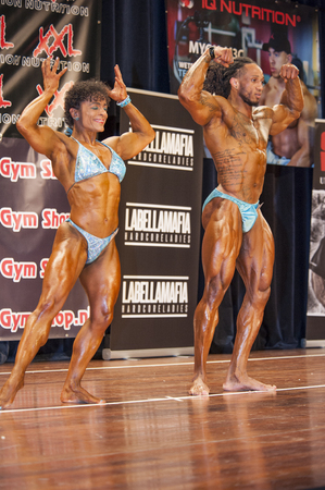 national championship: SCHIEDAM, THE NETHERLANDS - APRIL 26, 2015: Bodybuilding duo Floor van Putten and Grego Francisca show their best front double biceps pose on stage at the 38th Dutch National Championship Bodybuilding and Fitness of the IFBB Netherlands (NBBF) on april 26