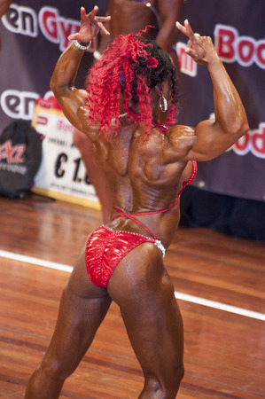 sch: SCHIEDAM, THE NETHERLANDS - APRIL 26, 2015: Female bikini model Lisandra Chacon shows her best back double biceps pose at the 38th Dutch National Championship Bodybuilding and Fitness of the IFBB Netherlands (NBBF) on april 26, 2015 in Theatre aan de Sch