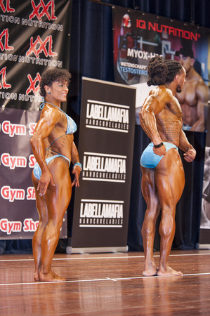 national championship: SCHIEDAM, THE NETHERLANDS - APRIL 26, 2015: Bodybuilding duo Floor van Putten and Grego Francisca show their relaxed side pose on stage at the 38th Dutch National Championship Bodybuilding and Fitness of the IFBB Netherlands (NBBF) on april 26, 2015 in Th