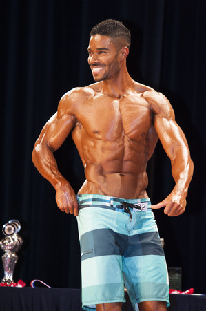 schiedam: SCHIEDAM, THE NETHERLANDS - APRIL 26, 2015. Male bodybuilder shows his best side chest pose on stage at the 38th Dutch National Championship Bodybuilding and Fitness of the IFBB Netherlands (NBBF) on april 26, 2015 in Theatre aan de Schie at Schiedam, t