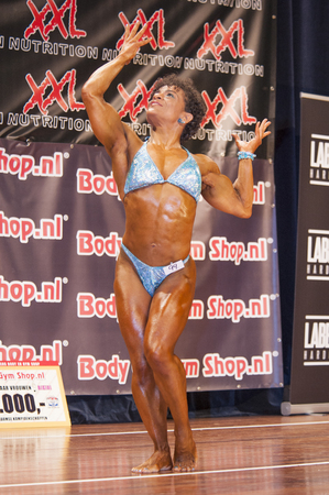 schiedam: SCHIEDAM, THE NETHERLANDS - APRIL 26, 2015: Female bodybuilder Floor van Putten shows her best muscular front double biceps pose variation on stage at the 38th Dutch National Championship Bodybuilding and Fitness of the IFBB Netherlands (NBBF) on april 26