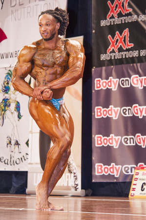 schiedam: SCHIEDAM, THE NETHERLANDS - APRIL 26, 2015. Male bodybuilder Grego Francisca shows his chest pose at the 38th Dutch National Championship Bodybuilding and Fitness of the IFBB Netherlands (NBBF) on april 26, 2015 in Theatre aan de Schie at Schiedam, the