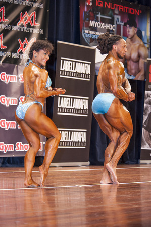 thea: SCHIEDAM, THE NETHERLANDS - APRIL 26, 2015: Bodybuilding duo Floor van Putten and Grego Francisca show their best chest pose on stage at the 38th Dutch National Championship Bodybuilding and Fitness of the IFBB Netherlands (NBBF) on april 26, 2015 in Thea
