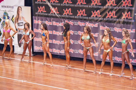 schiedam: SCHIEDAM, THE NETHERLANDS - APRIL 26, 2015: Female bikini models show their best side on stage in a lineup comparison during competition at the 38th Dutch National Championship Bodybuilding and Fitness of the IFBB Netherlands (NBBF) on april 26, 2015 in T