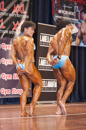 schiedam: SCHIEDAM, THE NETHERLANDS - APRIL 26, 2015: Bodybuilding duo Floor van Putten and Grego Francisca show their best triceps pose on stage at the 38th Dutch National Championship Bodybuilding and Fitness of the IFBB Netherlands (NBBF) on april 26, 2015 in Th
