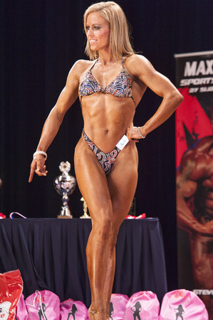 schiedam: SCHIEDAM, THE NETHERLANDS - APRIL 26, 2015: Female bikini modelLesley Barents shows her best front pose on stage at the 38th Dutch National Championship Bodybuilding and Fitness of the IFBB Netherlands (NBBF) on april 26, 2015 in Theatre aan de Schie at Editorial