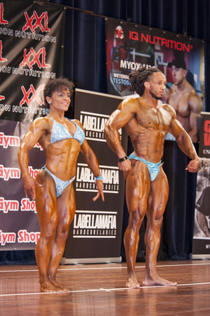 schiedam: SCHIEDAM, THE NETHERLANDS - APRIL 26, 2015: Bodybuilding duo Floor van Putten and Grego Francisca show their best relaxed front pose on stage at the 38th Dutch National Championship Bodybuilding and Fitness of the IFBB Netherlands (NBBF) on april 26, 2015