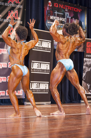 schiedam: SCHIEDAM, THE NETHERLANDS - APRIL 26, 2015: Bodybuilding duo Floor van Putten and Grego Francisca show their best back double biceps pose on stage at the 38th Dutch National Championship Bodybuilding and Fitness of the IFBB Netherlands (NBBF) on april 26, Editorial