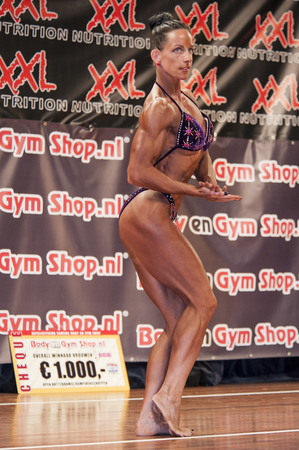 schiedam: SCHIEDAM, THE NETHERLANDS - APRIL 26, 2015: Female bikini fitness and physique model Mariska Meuwissen shows her fit and toned body on stage at the 38th Dutch National Championship Bodybuilding and Fitness of the IFBB Netherlands (NBBF) on april 26, 2015