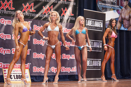 schiedam: SCHIEDAM, THE NETHERLANDS - APRIL 26, 2015: Female bikini models showing their best in a lineup comparisonat the 38th Dutch National Championship Bodybuilding and Fitness of the IFBB Netherlands (NBBF) on april 26, 2015 in Theatre aan de Schie at Schied