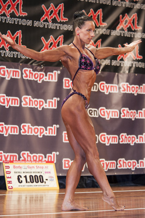 schiedam: SCHIEDAM, THE NETHERLANDS - APRIL 26, 2015: Female bikini fitness and physique model Mariska Meuwissen shows her fit and muscular body at the 38th Dutch National Championship Bodybuilding and Fitness of the IFBB Netherlands (NBBF) on april 26, 2015 in The Editorial