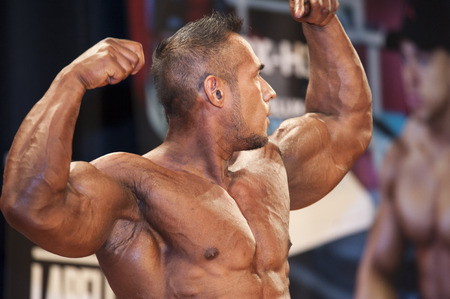 schiedam: SCHIEDAM, THE NETHERLANDS - APRIL 26, 2015. Male bodybuilder shows his best front double biceps at the 38th Dutch National Championship Bodybuilding and Fitness of the IFBB Netherlands (NBBF) on april 26, 2015 in Theatre aan de Schie at Schiedam, the Ne