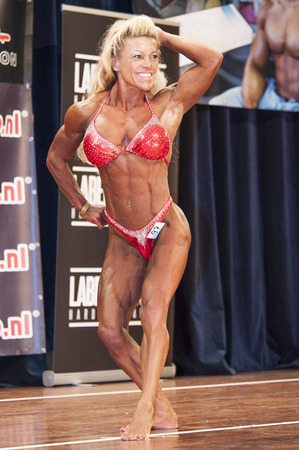 schiedam: SCHIEDAM, THE NETHERLANDS - APRIL 26, 2015: Female bikini fitness model Sylvia Thijssen shows her best abdominals and thighs pose at the 38th Dutch National Championship Bodybuilding and Fitness of the IFBB Netherlands (NBBF) on april 26, 2015 in Theatre  Editorial