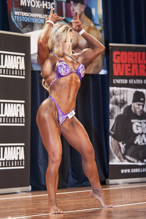 schiedam: SCHIEDAM, THE NETHERLANDS - APRIL 26, 2015: Female bikini fitness model Evelien Nellen shows her best front double biceps pose on stage at the 38th Dutch National Championship Bodybuilding and Fitness of the IFBB Netherlands (NBBF) on april 26, 2015 in Th