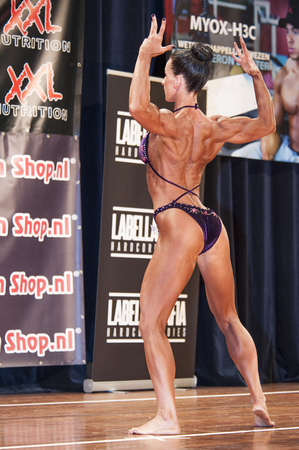 schiedam: SCHIEDAM, THE NETHERLANDS - APRIL 26, 2015: Female bikini fitness and physique model Mariska Meuwissen shows her best back double biceps pose at the 38th Dutch National Championship Bodybuilding and Fitness of the IFBB Netherlands (NBBF) on april 26, 2015 Editorial