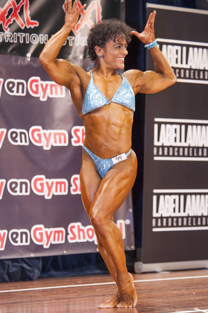 schiedam: SCHIEDAM, THE NETHERLANDS - APRIL 26, 2015: Female bikini fitness model Floor van Putten shows her best front double biceps pose at the 38th Dutch National Championship Bodybuilding and Fitness of the IFBB Netherlands (NBBF) on april 26, 2015 in Theatre