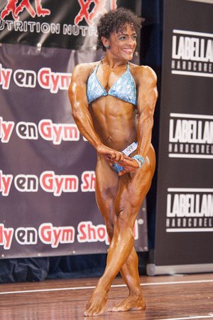 schiedam: SCHIEDAM, THE NETHERLANDS - APRIL 26, 2015: Female bikini fitness model Floor van Putten shows her best triceps pose at the 38th Dutch National Championship Bodybuilding and Fitness of the IFBB Netherlands (NBBF) on april 26, 2015 in Theatre aan de Schie Editorial