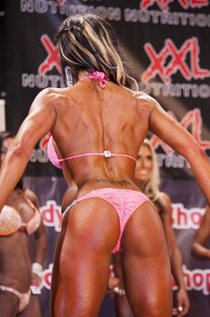 schiedam: SCHIEDAM, THE NETHERLANDS - APRIL 26, 2015: Female bodyfitness and bikini model in pink bikini shows her best back pose at the 38th Dutch National Championship Bodybuilding and Fitness of the IFBB Netherlands (NBBF) on april 26, 2015 in Theatre aan de Sc Editorial