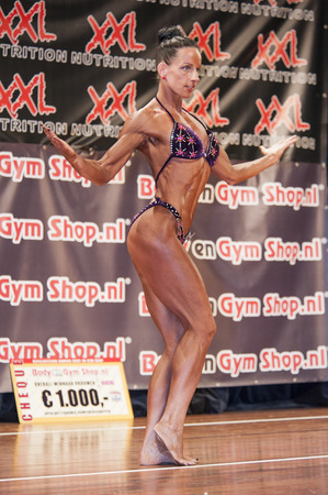 schiedam: SCHIEDAM, THE NETHERLANDS - APRIL 26, 2015: Female bikini fitness and physique model Mariska Meuwissen shows her fit and toned body at the 38th Dutch National Championship Bodybuilding and Fitness of the IFBB Netherlands (NBBF) on april 26, 2015 in Theatr