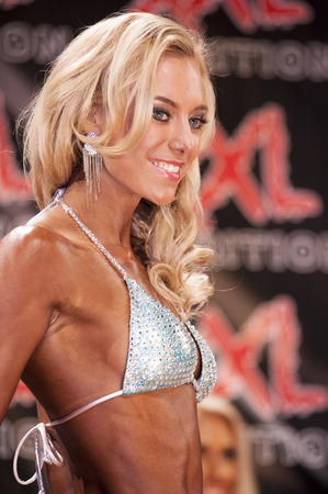 schiedam: SCHIEDAM, THE NETHERLANDS - APRIL 26, 2015: Blond female bodyfitness and bikini model shows her best at the 38th Dutch National Championship Bodybuilding and Fitness of the IFBB Netherlands (NBBF) on april 26, 2015 in Theatre aan de Schie at Schiedam, t
