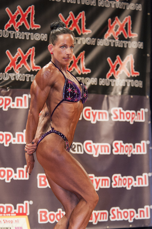 schiedam: SCHIEDAM, THE NETHERLANDS - APRIL 26, 2015: Female bikini fitness and physique model Mariska Meuwissen shows her best triceps pose at the 38th Dutch National Championship Bodybuilding and Fitness of the IFBB Netherlands (NBBF) on april 26, 2015 in Theatre
