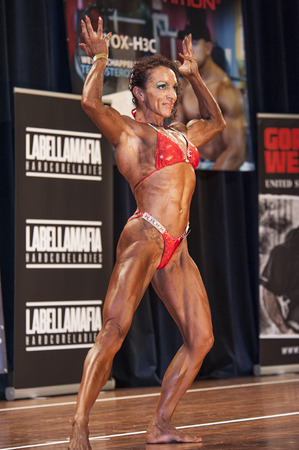 schiedam: SCHIEDAM, THE NETHERLANDS - APRIL 26, 2015: Female bikini fitness and physique model Naima Benamari shows her best front double biceps pose on stage at the 38th Dutch National Championship Bodybuilding and Fitness of the IFBB Netherlands (NBBF) on april 2 Editorial
