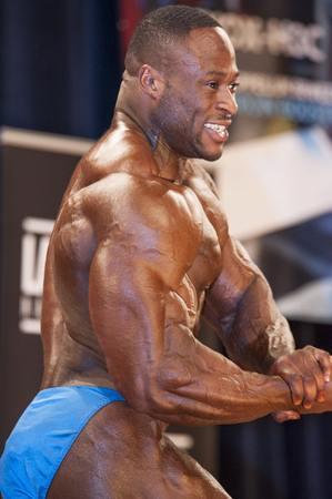 schiedam: SCHIEDAM, THE NETHERLANDS - APRIL 26, 2015. Male bodybuilder Michael Muzo shows his best chest pose on stage at the 38th Dutch National Championship Bodybuilding and Fitness of the IFBB Netherlands (NBBF) on april 26, 2015 in Theatre aan de Schie at Sch