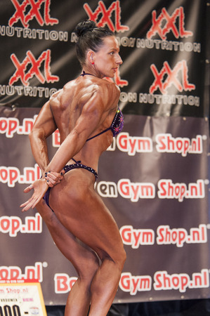 schiedam: SCHIEDAM, THE NETHERLANDS - APRIL 26, 2015: Female bikini fitness and physique model Mariska Meuwissen shows her best triceps pose on stage at the 38th Dutch National Championship Bodybuilding and Fitness of the IFBB Netherlands (NBBF) on april 26, 2015 i