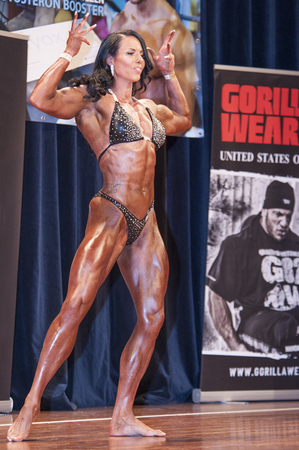 schiedam: SCHIEDAM, THE NETHERLANDS - APRIL 26, 2015: Female bikini model, power amazon and muscle lady Maria Wattel shows her best front double biceps pose at the 38th Dutch National Championship Bodybuilding and Fitness of the IFBB Netherlands (NBBF) on april 26, Editorial