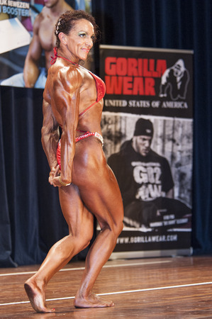 schiedam: SCHIEDAM, THE NETHERLANDS - APRIL 26, 2015: Female bikini fitness and physique model Naima Benamari shows her best triceps pose at the 38th Dutch National Championship Bodybuilding and Fitness of the IFBB Netherlands (NBBF) on april 26, 2015 in Theatre a